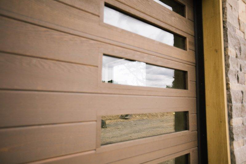 Close up of custom wood garage door with vertical windows